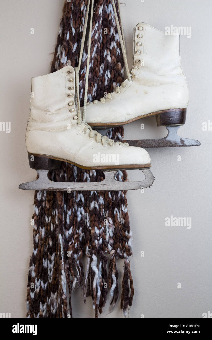 Pair of old white ice skates hanging with brown and blue scarf - Stock Image