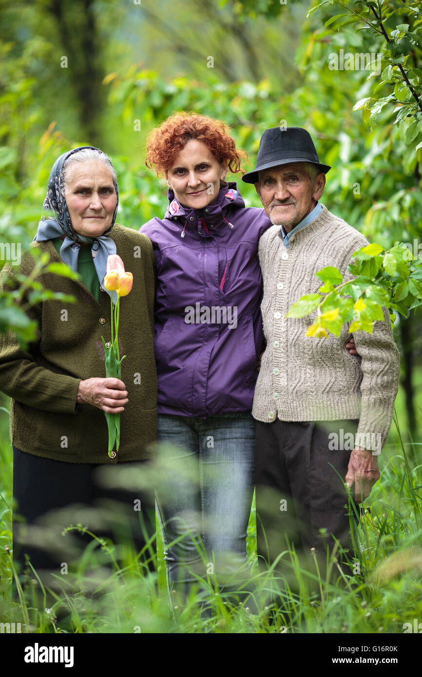 European woman and her old parents in the garden - Stock Image