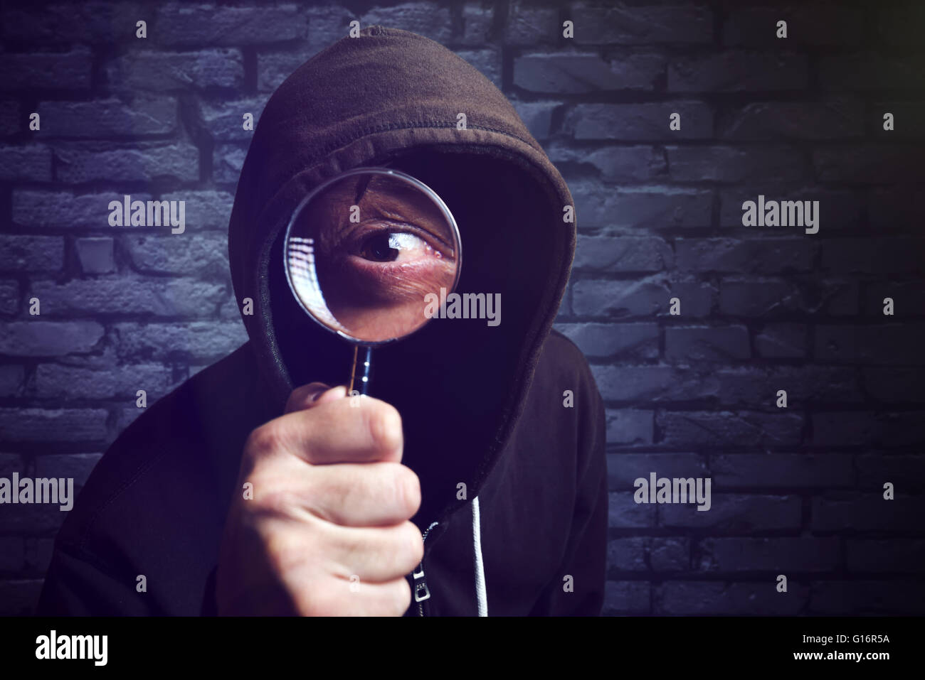 Hooded computer hacker with magnifying glass, internet hacker and online security concept. - Stock Image