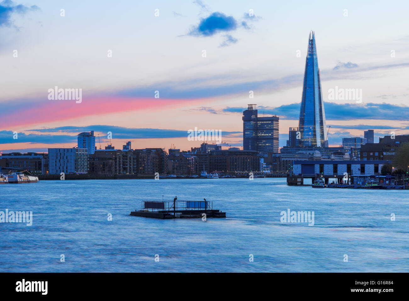Modern London cityscape during sunset with a pink stripe in sky - Stock Image