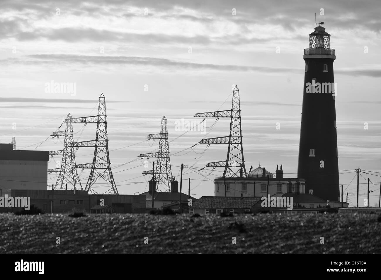 Dungeness Lighthouse with electricity pylons and power station. - Stock Image