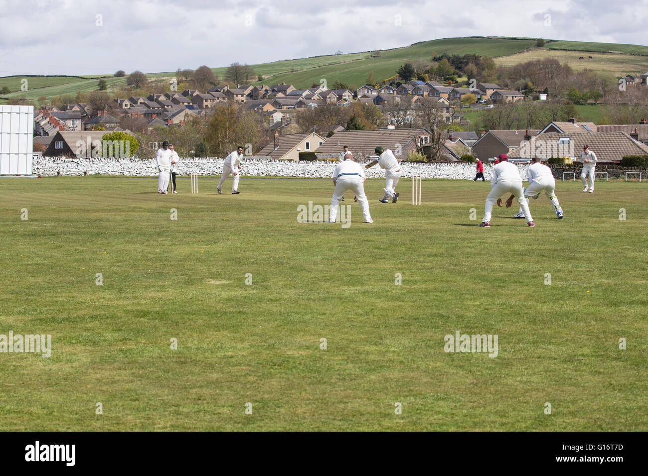 English village cricket match with bowler delivering ball to a batsman - Stock Image