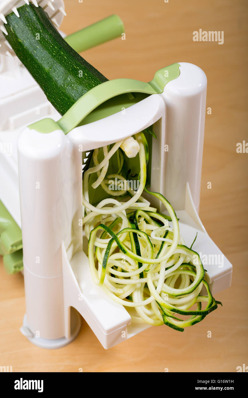 Making courgette (Zucchini) noodles (spaghetti) with a spiralizer Stock Photo