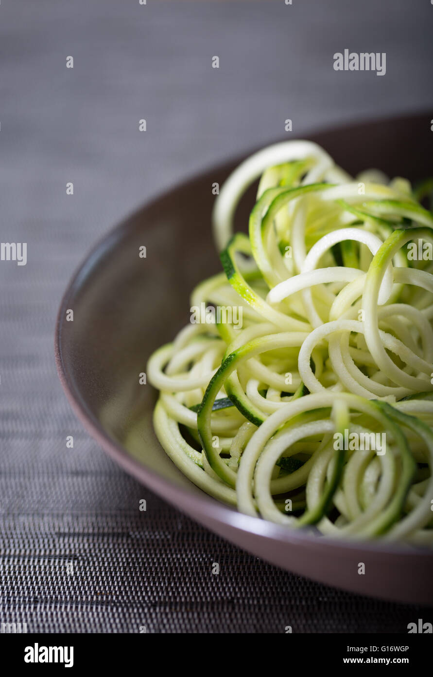 A bowl of courgette (Zucchini) noodles (spaghetti) made using a spiralizer - Stock Image