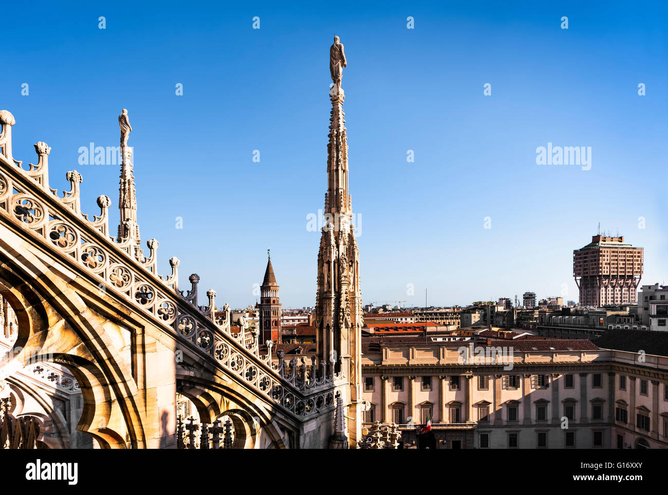 White marble statues on the roof of famous Cathedral Duomo di Milano on piazza in Milan, Italy - Stock Image