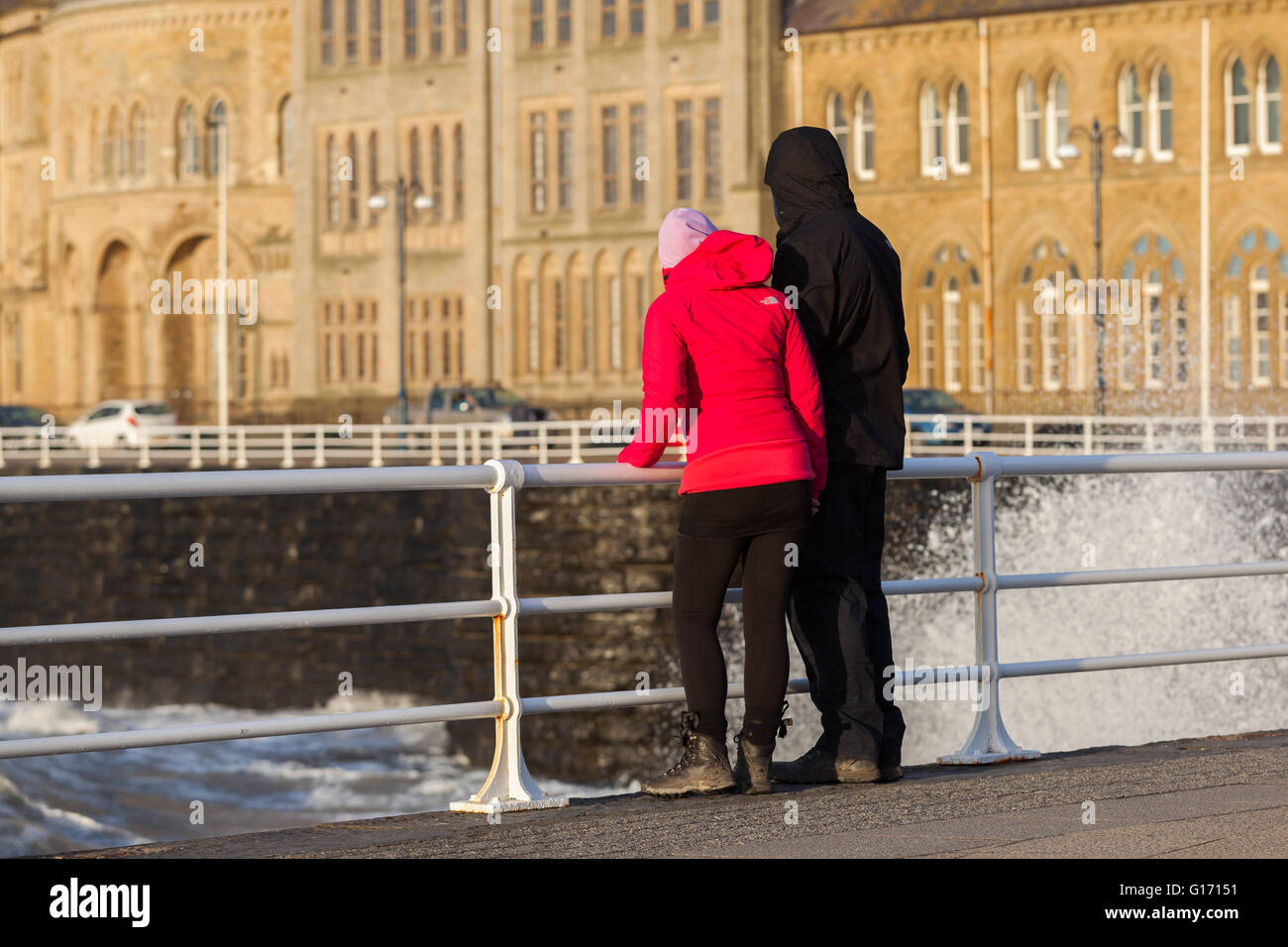 A couple looking over railings on a promenade - Stock Image