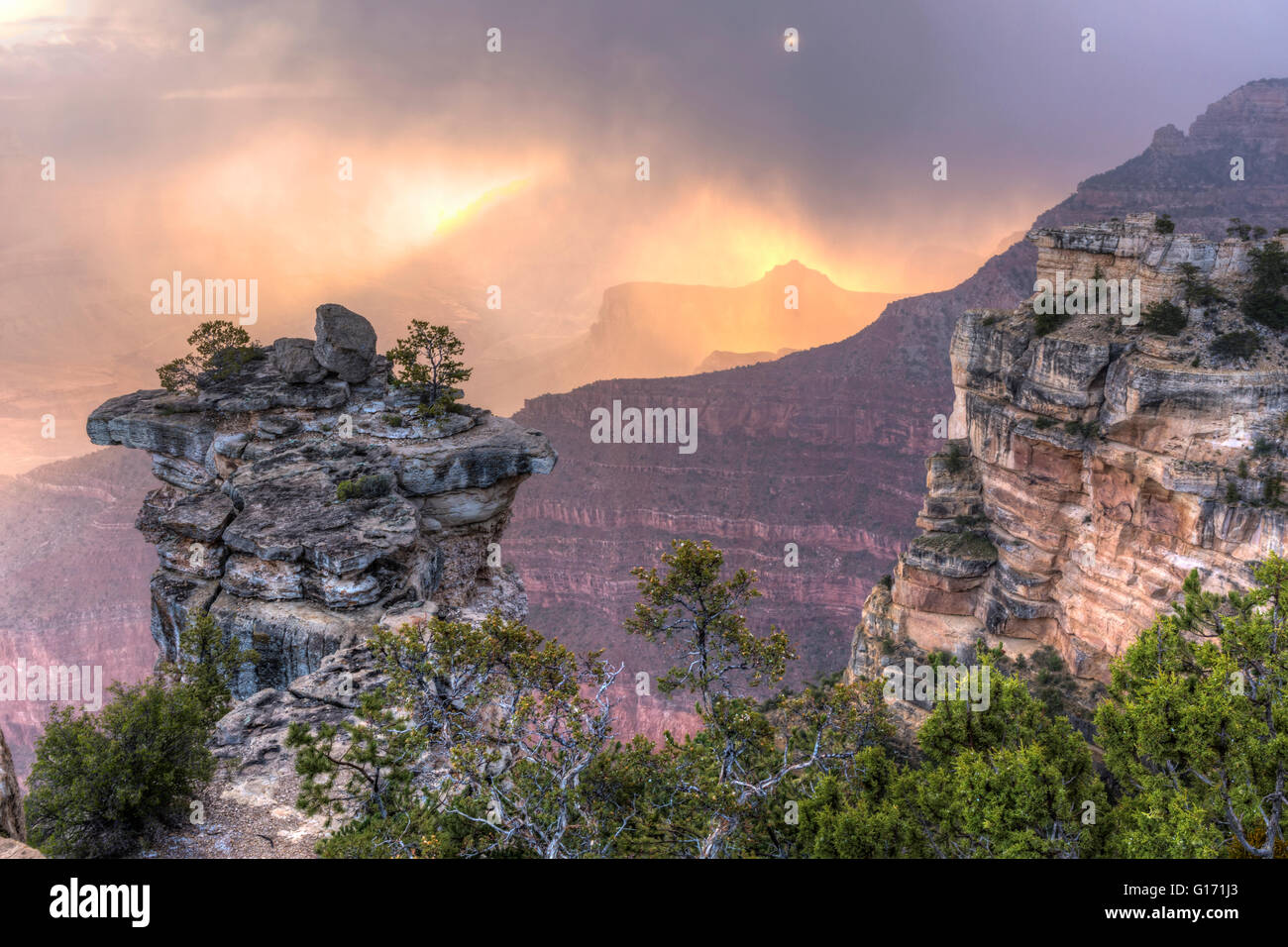 The sun lights up the low clouds and swirling snow seen from Mather Point in Grand Canyon National Park, Arizona. - Stock Image