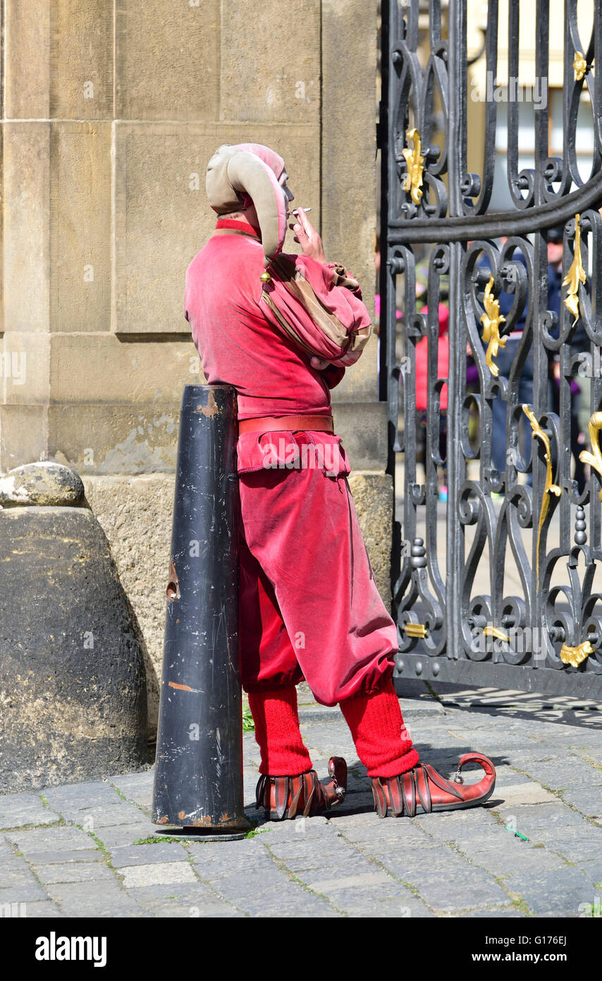 Prague, Czech Republic. Man dressed as a jester pausing for a cigarette at the castle gates - Stock Image
