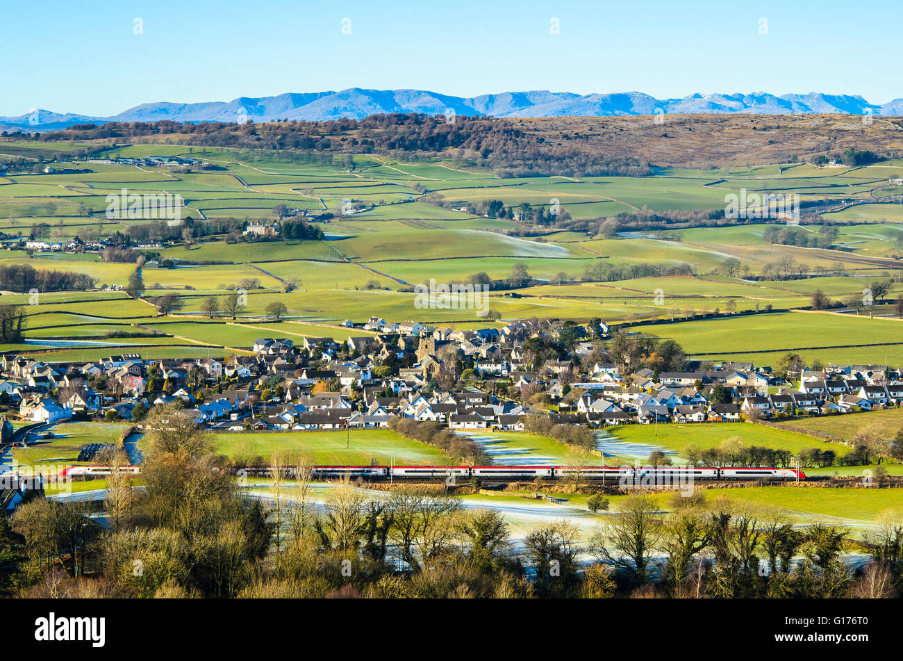 Virgin Pendolino train on West Coast Main Line passing the village of Natland near Kendal Cumbria with Lakeland - Stock Image