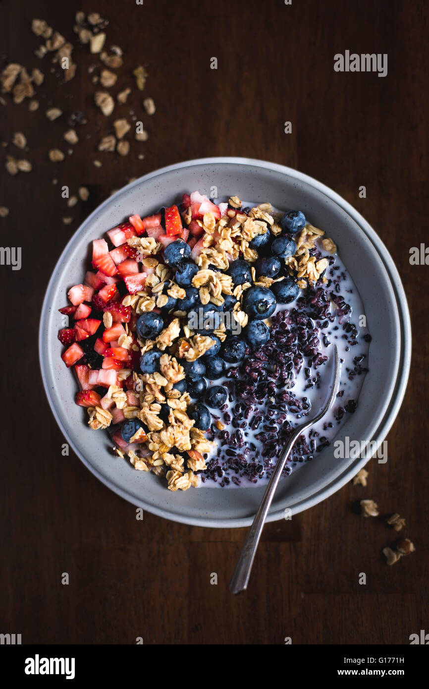 A bowl of Forbidden Rice Morning Cereal with Berries and granola is photographed from the top. - Stock Image
