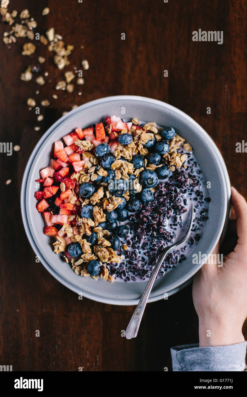 A woman's hand is on the side of a forbidden rice morning cereal with berries. She is about to eat it for breakfast. - Stock Image