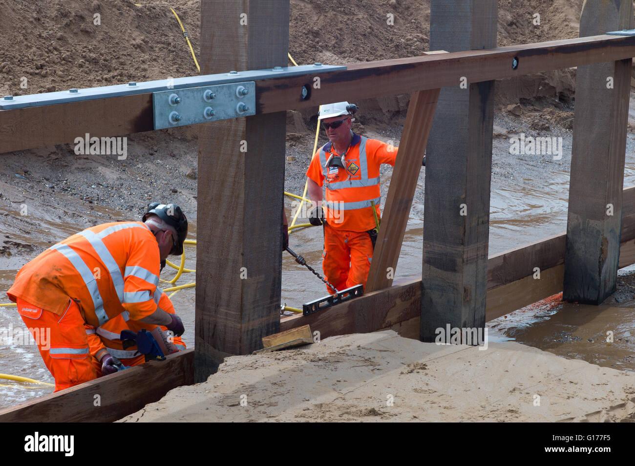 Workmen rebuilding the groins on Dawlish beach in South Devon UK. This area has had big coastal erosion problems - Stock Image