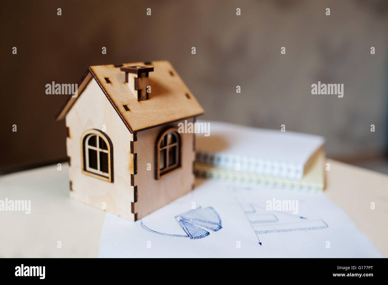 Real estate concept wooden toy house with paper diagram - Stock Image