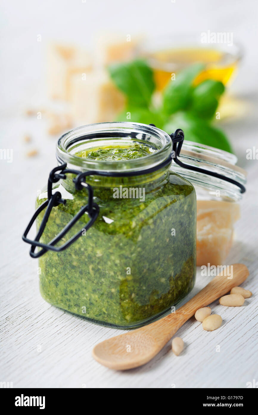 Homemade traditional basil pesto and ingredients on a rustic wooden table Stock Photo