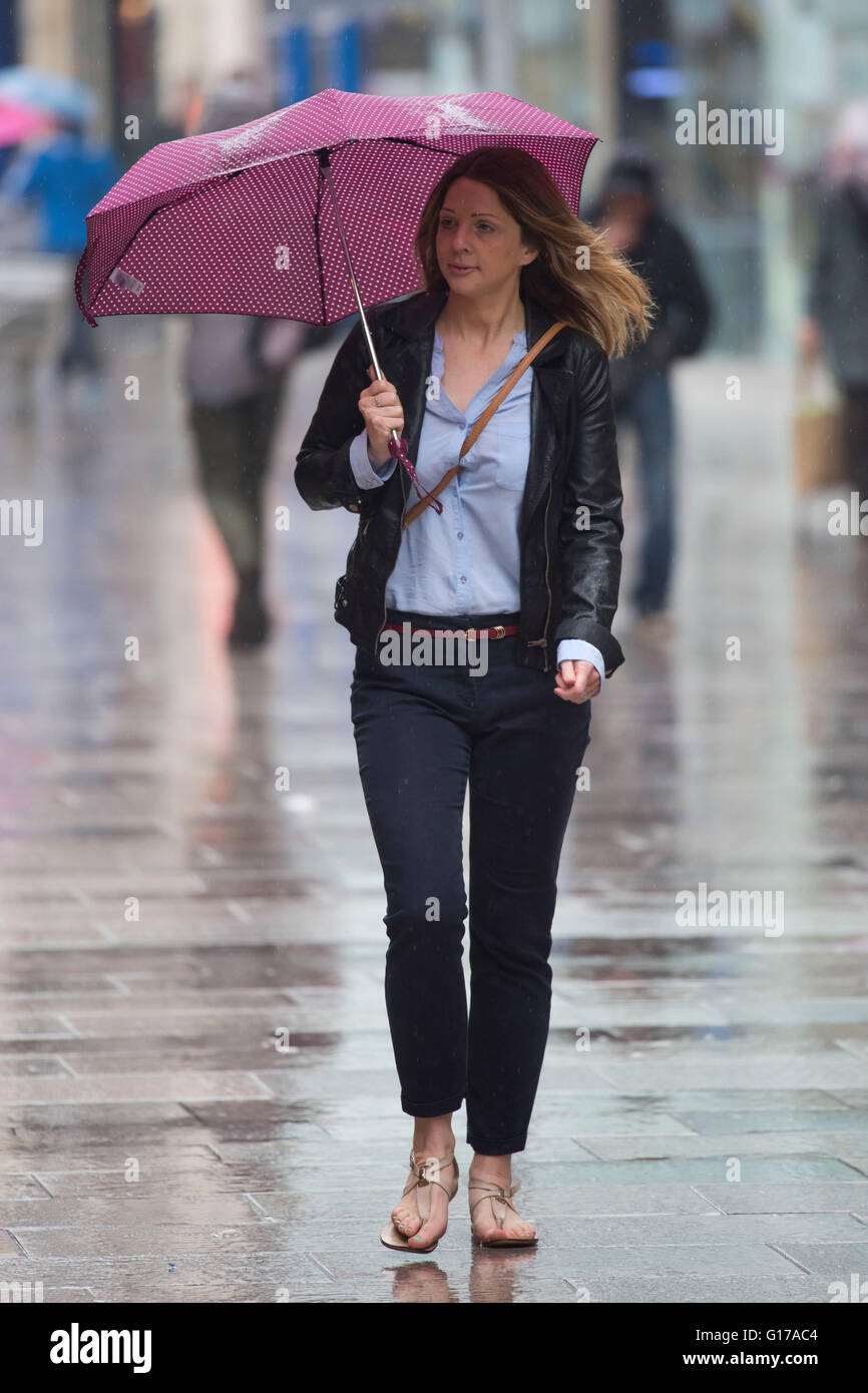 A woman carries an umbrella during heavy rain. - Stock Image