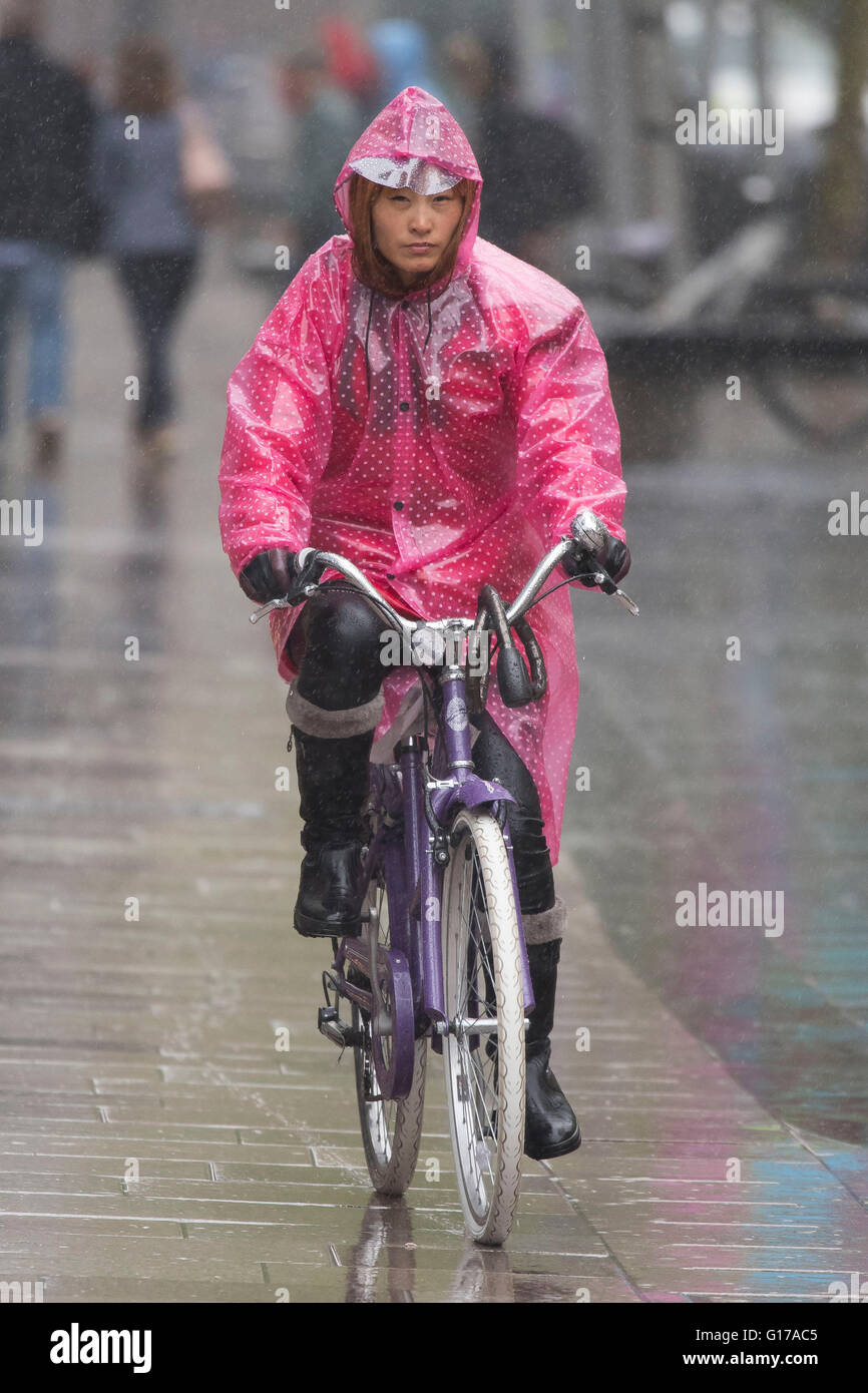 An Asian woman wears a pink poncho while riding a bike during wet weather in Cardiff, Wales. - Stock Image