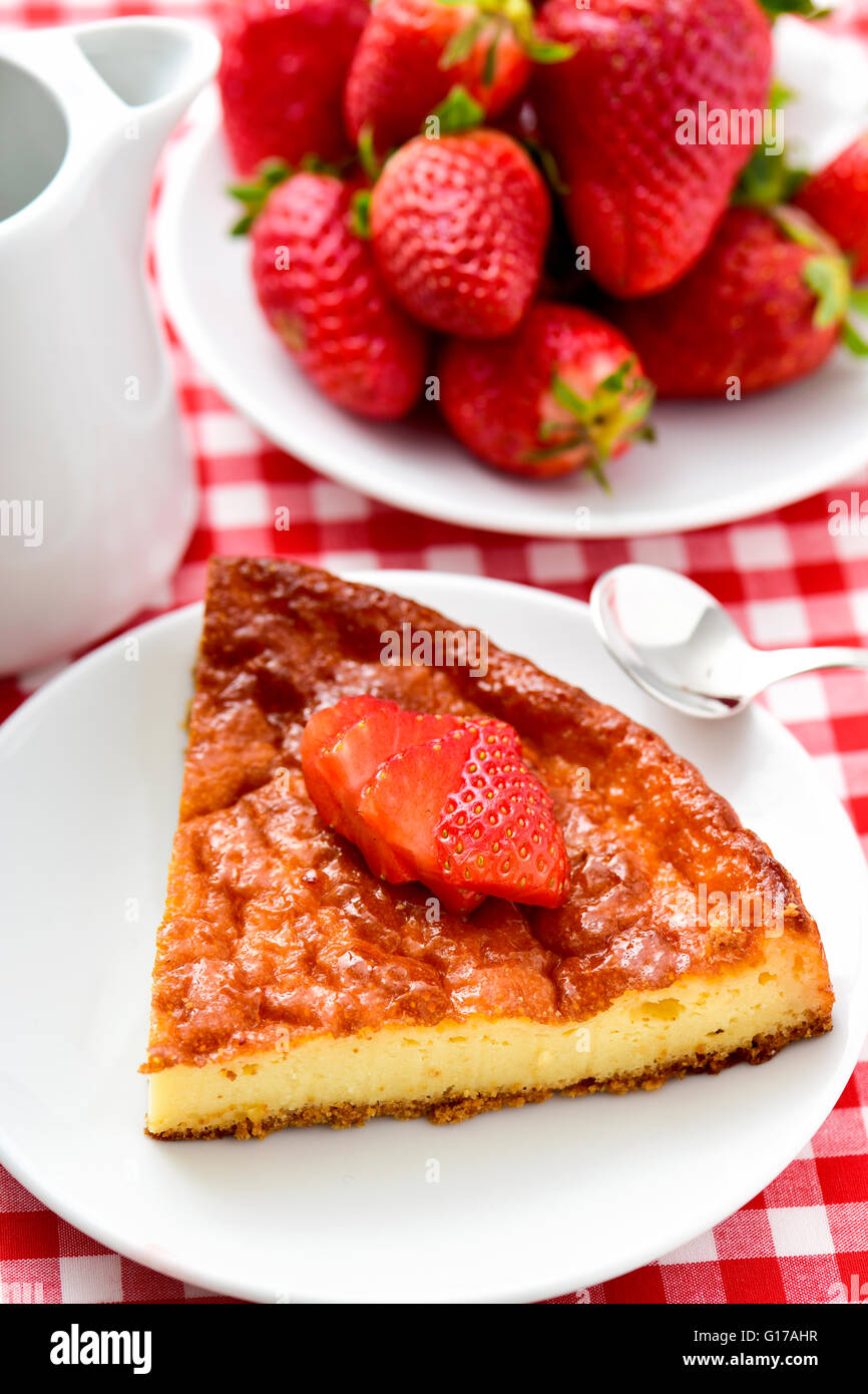 a plate with a piece of homemade cheesecake topped with sliced strawberry and a plate with ripe strawberries on - Stock Image