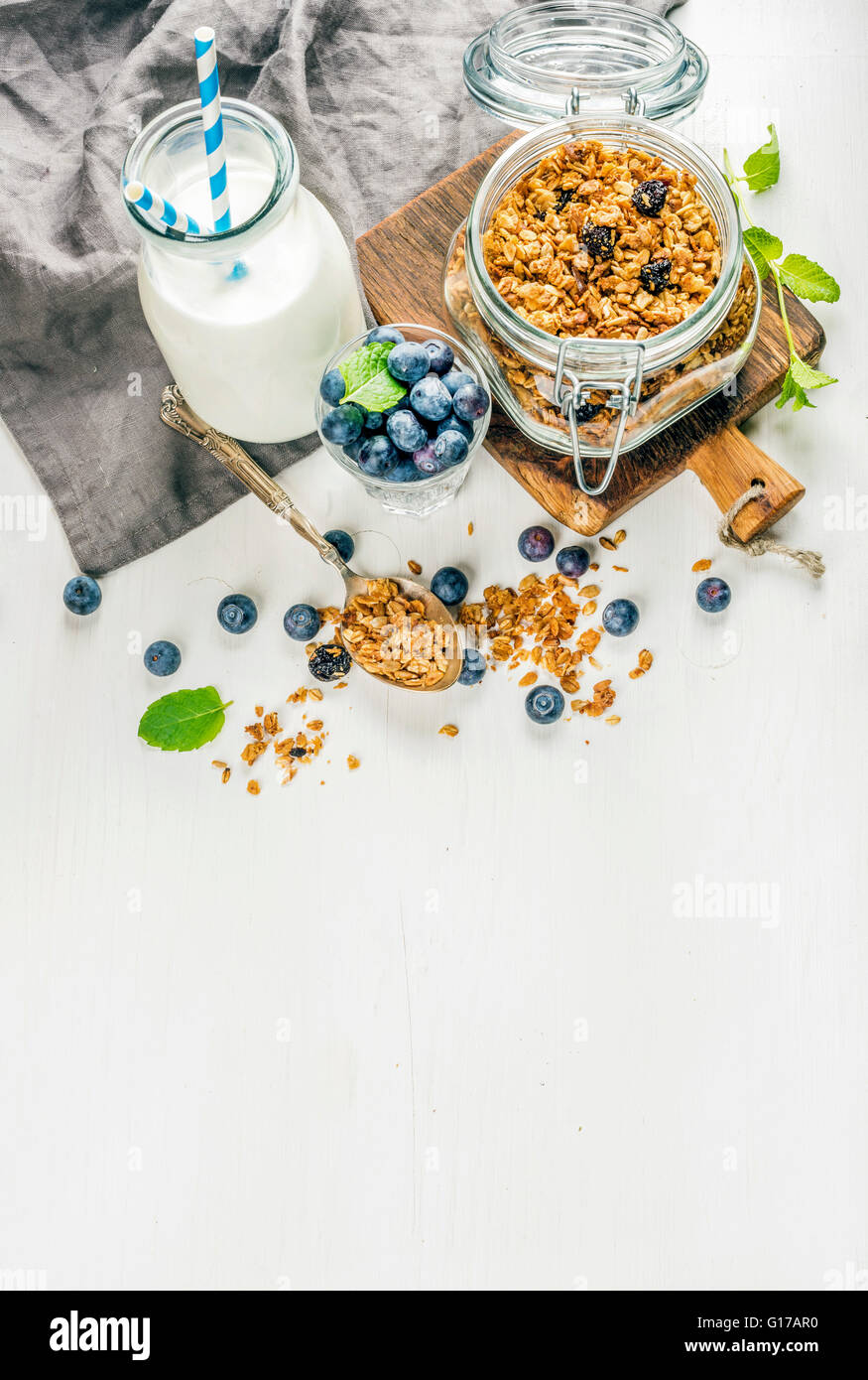 Healthy breakfast ingrediens. Homemade granola in open glass jar, milk or yogurt bottle, blueberries and mint on - Stock Image