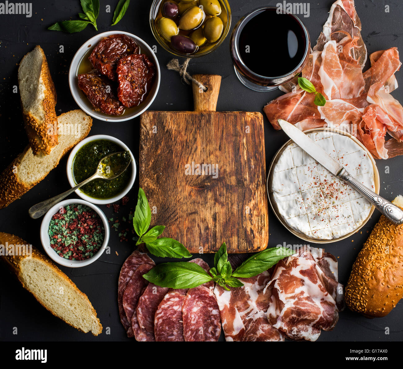 Wine snack set with empty wooden board in center. Glass of red, meat selection, mediterranean olives, sun-dried - Stock Image