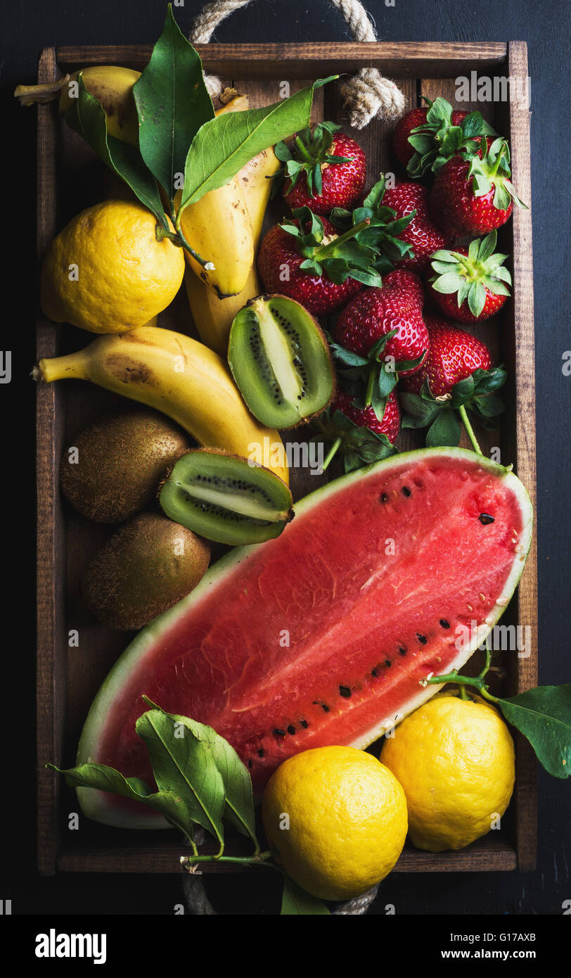 Various colorful tropical fruit selection in wooden tray over dark background, top view. Watermelon, strawberry, - Stock Image