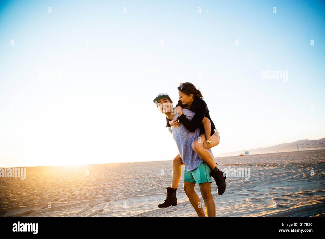 Young man giving girlfriend a piggy back at beach, Venice Beach, California, USA - Stock Image