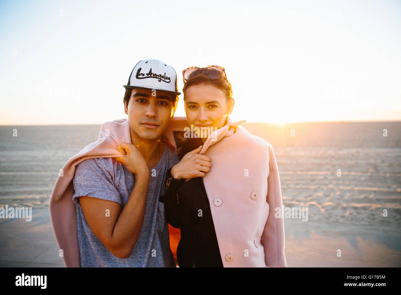 Portrait of young couple wrapped in overcoat on beach, Venice Beach, California, USA - Stock Image