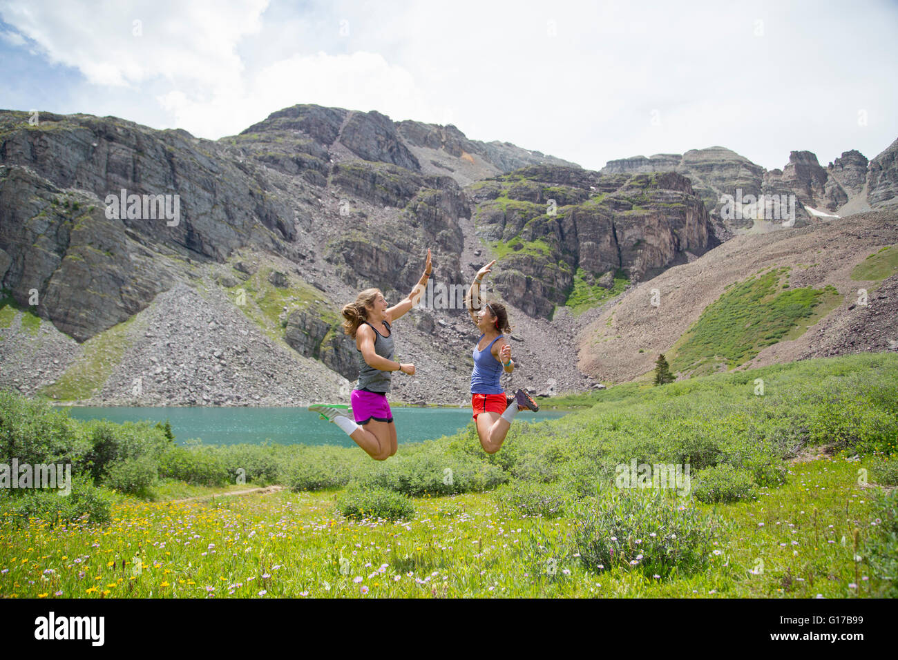 Women rejoicing in mid air, Cathedral Lake, Aspen, Colorado - Stock Image