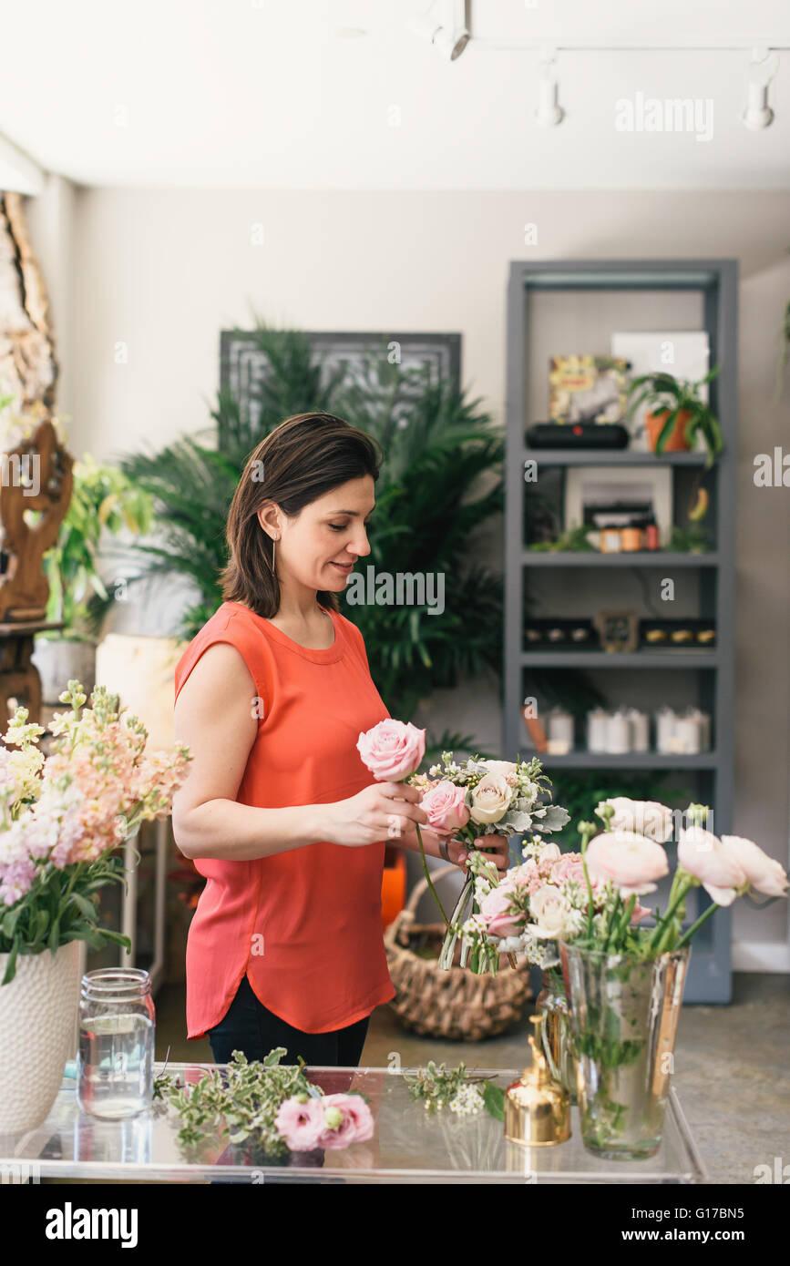 Florist arranging bouquet in flower shop - Stock Image