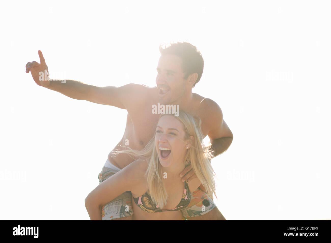 Woman giving man piggyback looking away smiling - Stock Image