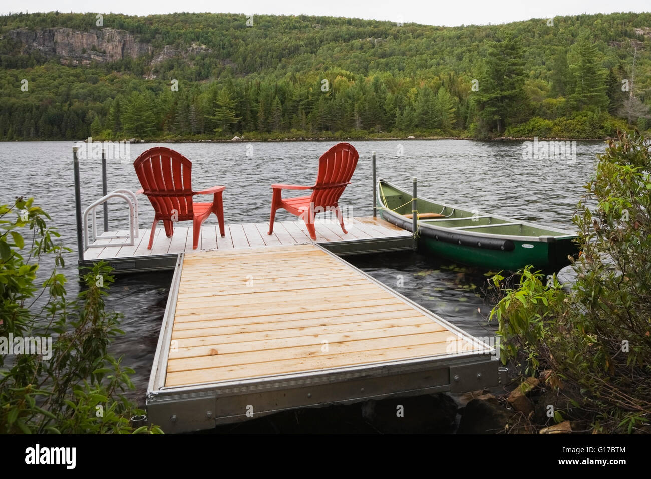 Superbe Two Red Adirondack Chairs On Floating Dock On River