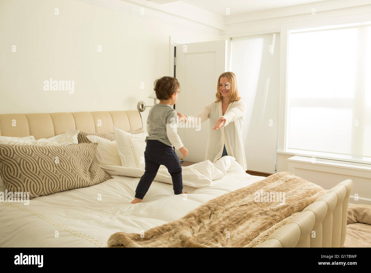 Woman opening arms to toddler son on bed - Stock Image