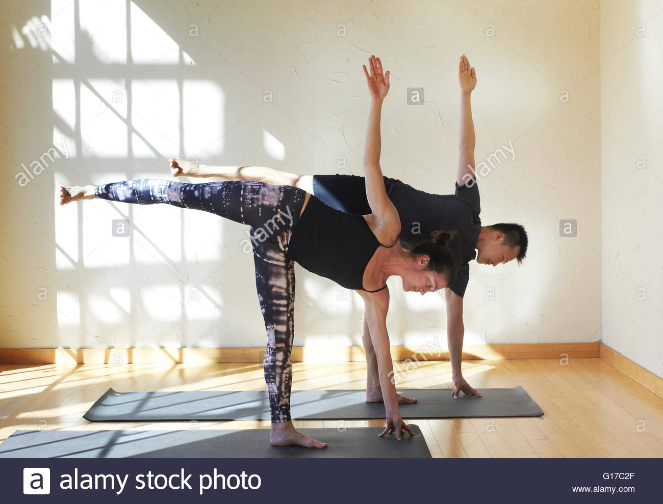 Man and woman doing yoga in studio, in half moon position - Stock Image