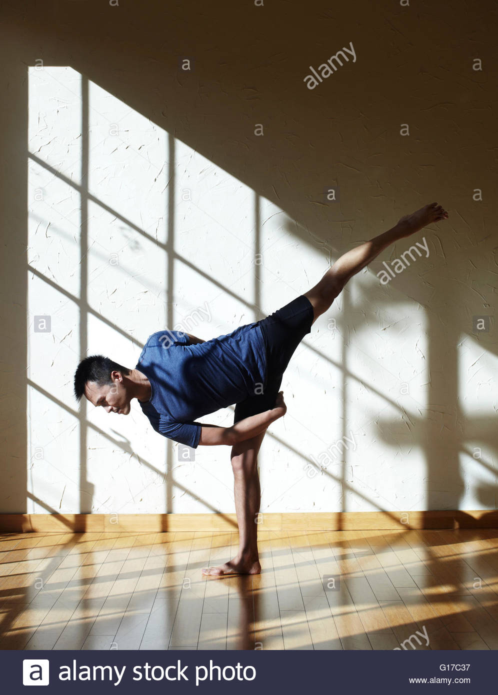 Man doing yoga in studio, in half moon bind position - Stock Image