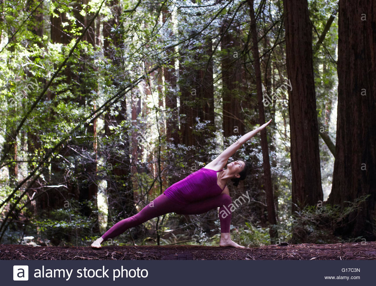 Mid adult woman doing yoga in forest, in extended side angle pose Stock Photo