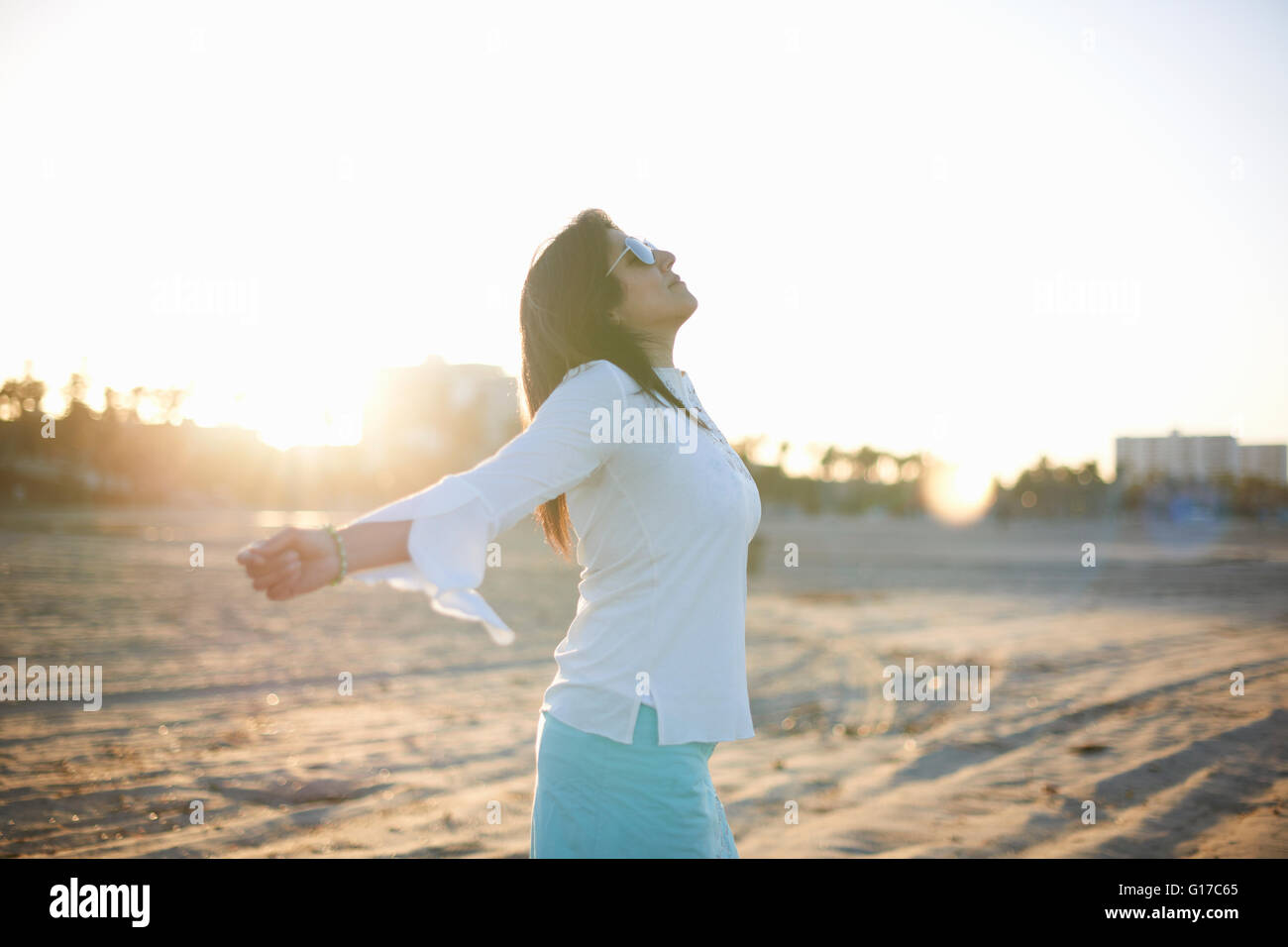 Woman with arms open on Santa Monica beach at sunset, Cresent City, California, USA - Stock Image