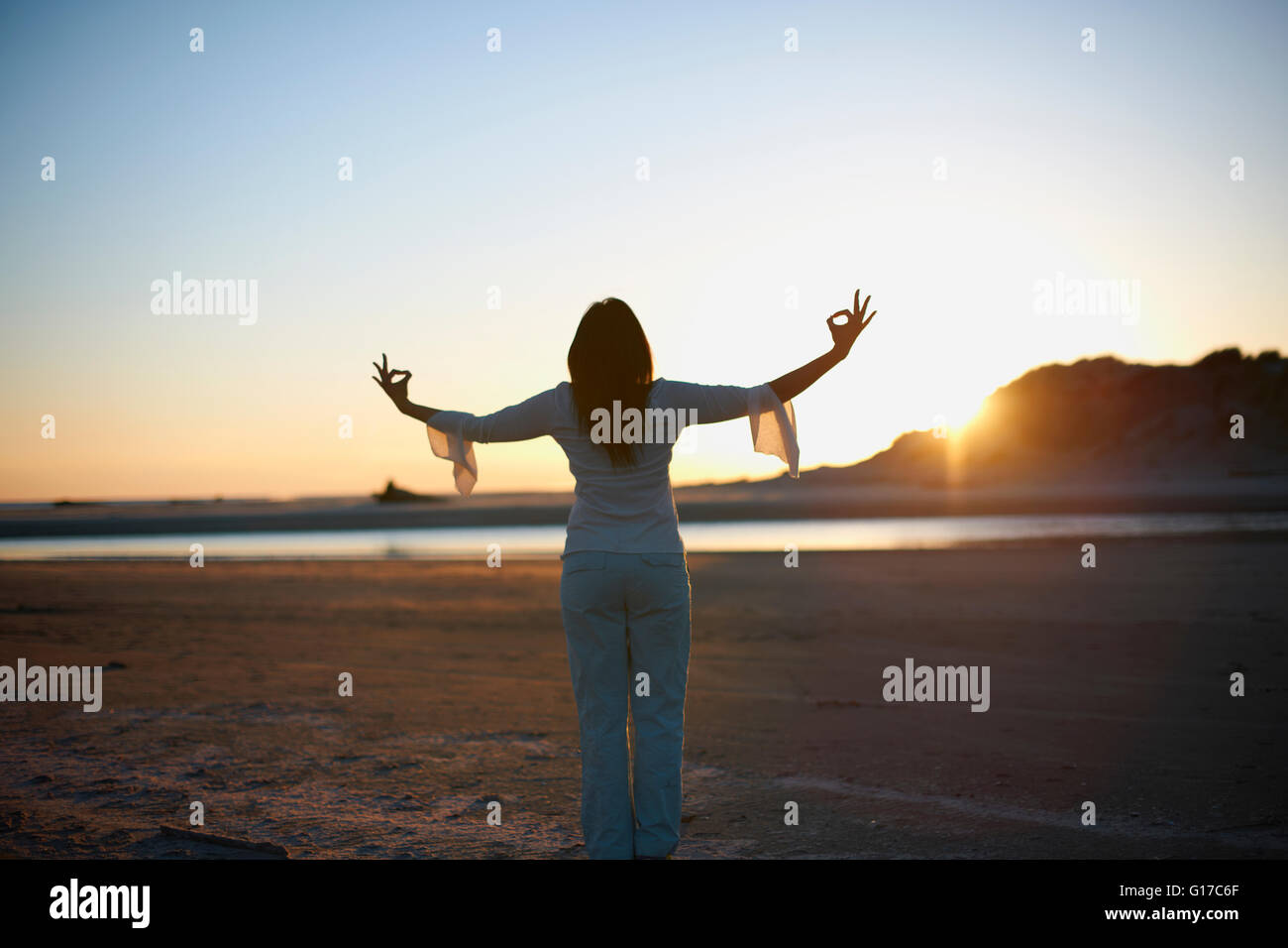 Rear view of woman with arms open on Cannon Beach at sunset, California, USA - Stock Image