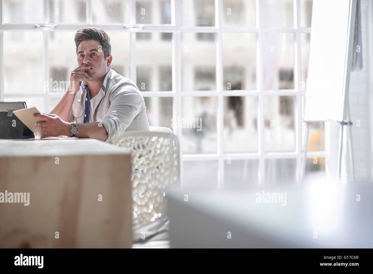 Businessman contemplating in office - Stock Image