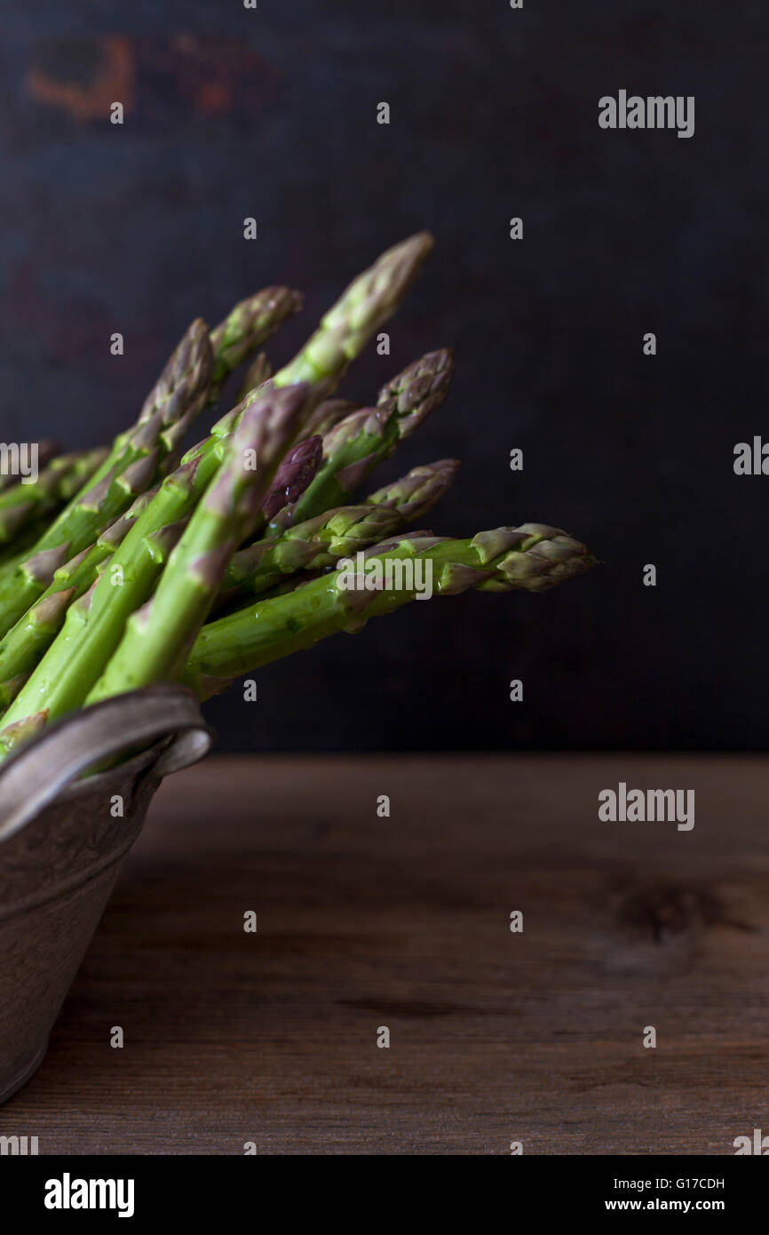 Fresh green asparagus in an old bucket on a rustic wooden table - Stock Image