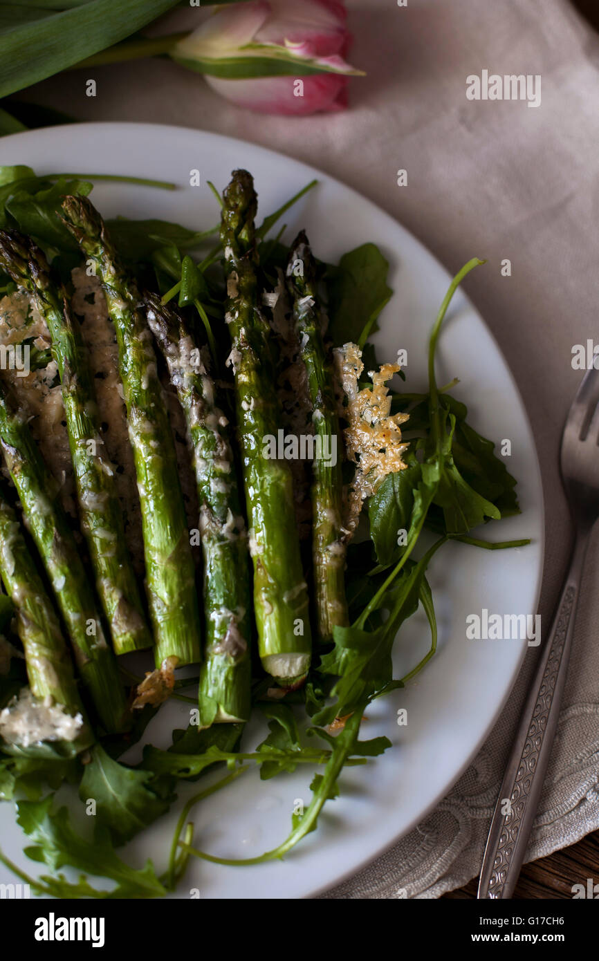 Roasted asparagus with Parmesan cheese on a bed of rucola salad - Stock Image