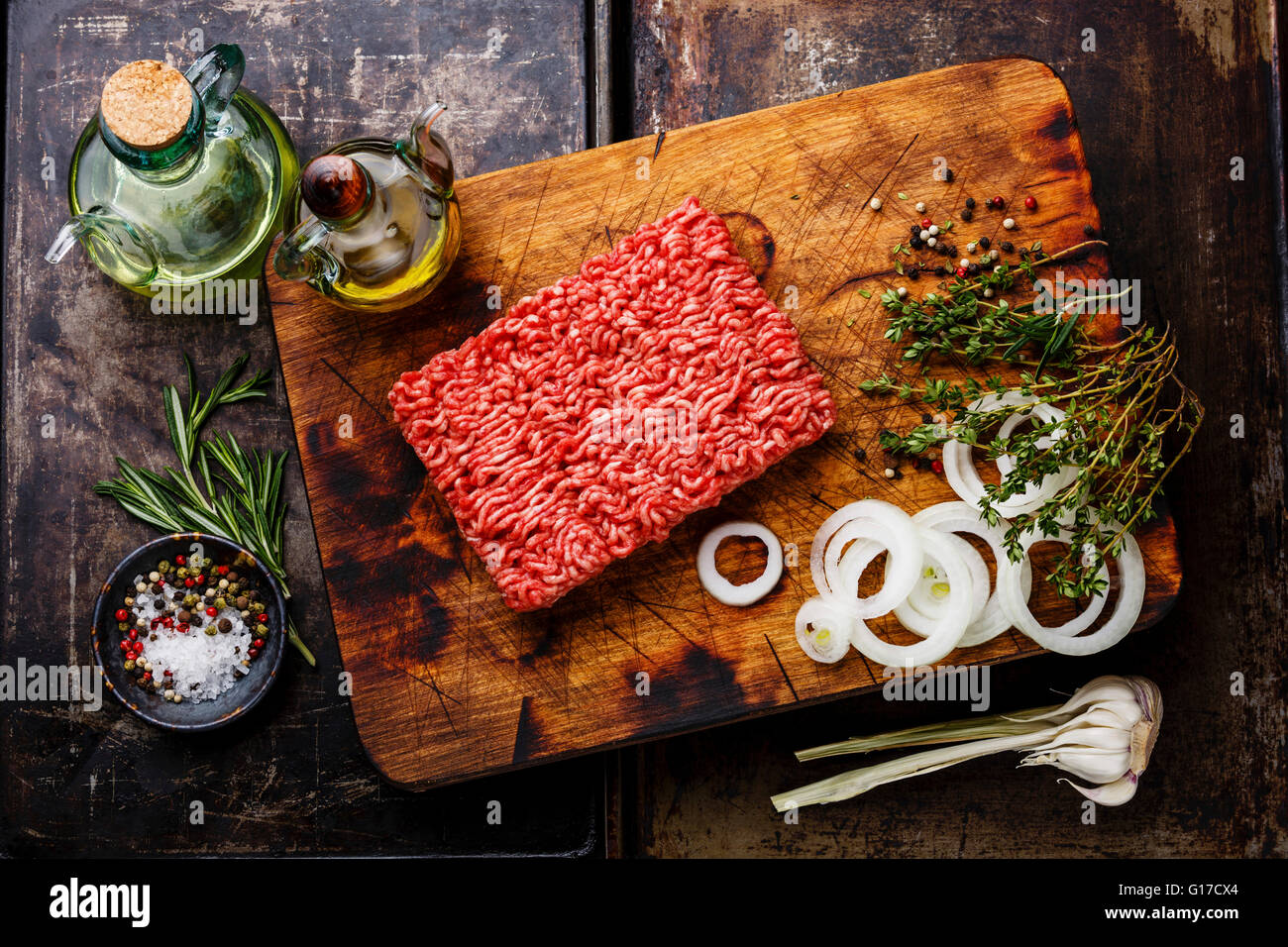 Raw fresh Minced ground meat and condiments on dark background - Stock Image