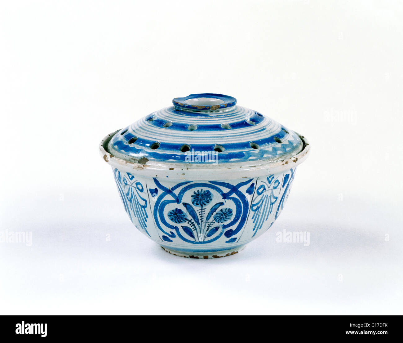 Tin-glazed earthenware flower or pot-pourri holder and lid, with blue and manganese painted decoration of stylised - Stock Image