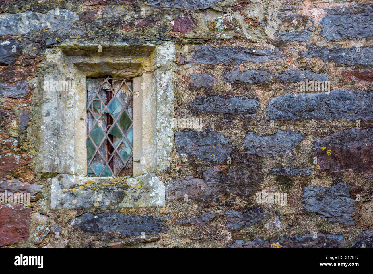 A old stone church window with stained glass and lead work in Cockington Village Church, Torquay, Devon, UK - Stock Image