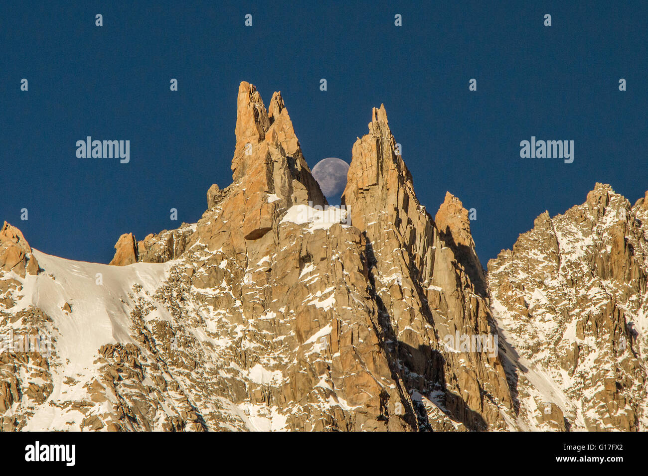 The perfect alignment of the moon between two rocky peaks - Stock Image