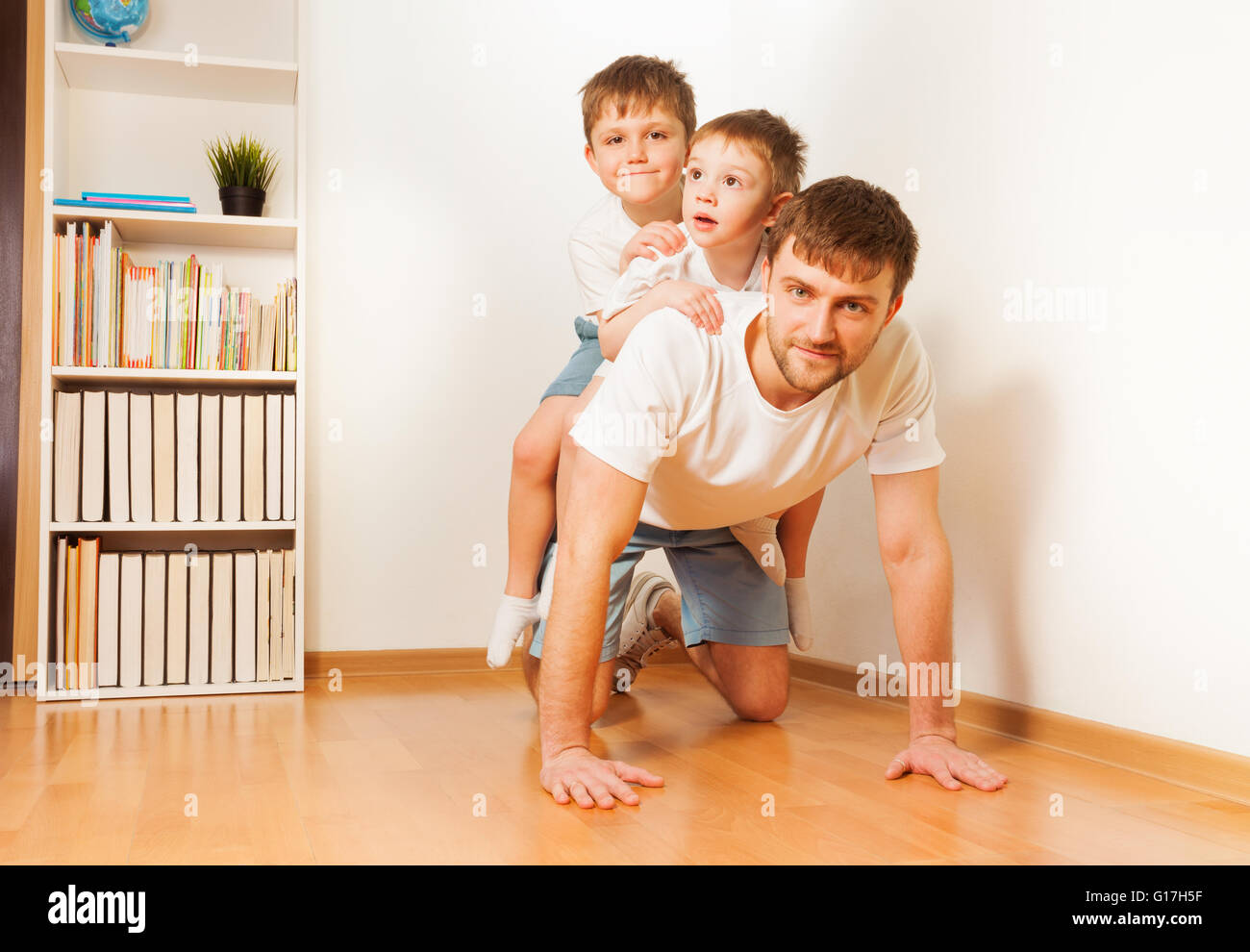 Father giving his two sons piggy back ride - Stock Image