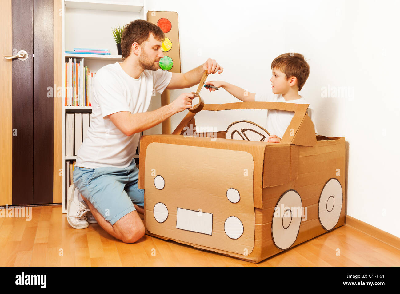 Father And His Son Making Toy Car Of Cardboard Box Stock