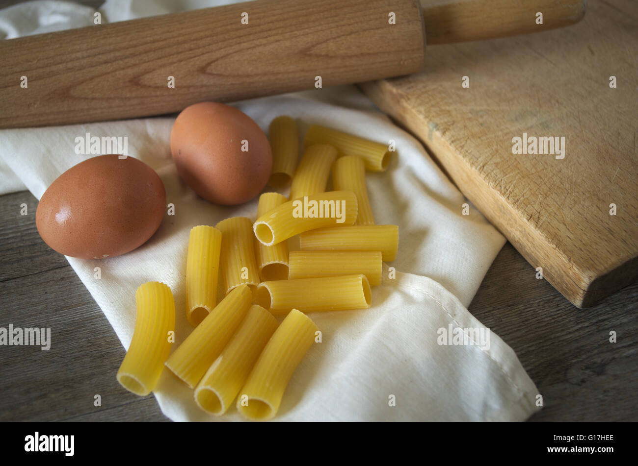 Italian food. Pasta (rigatoni) with eggs on wooden table in low light Stock Photo