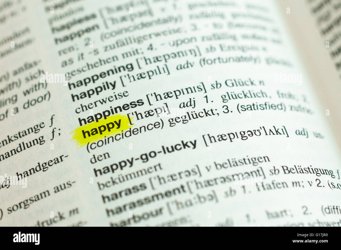 Detail of English word 'happy' and its german translation from dictionary - Stock Image