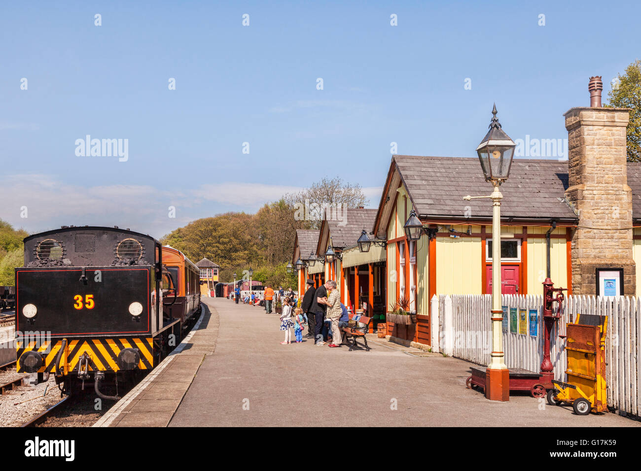 People waiting on the platform at Bolton Abbey Station as  0-6-0 Austerity Class Saddle Tank Engine arrives, showing - Stock Image