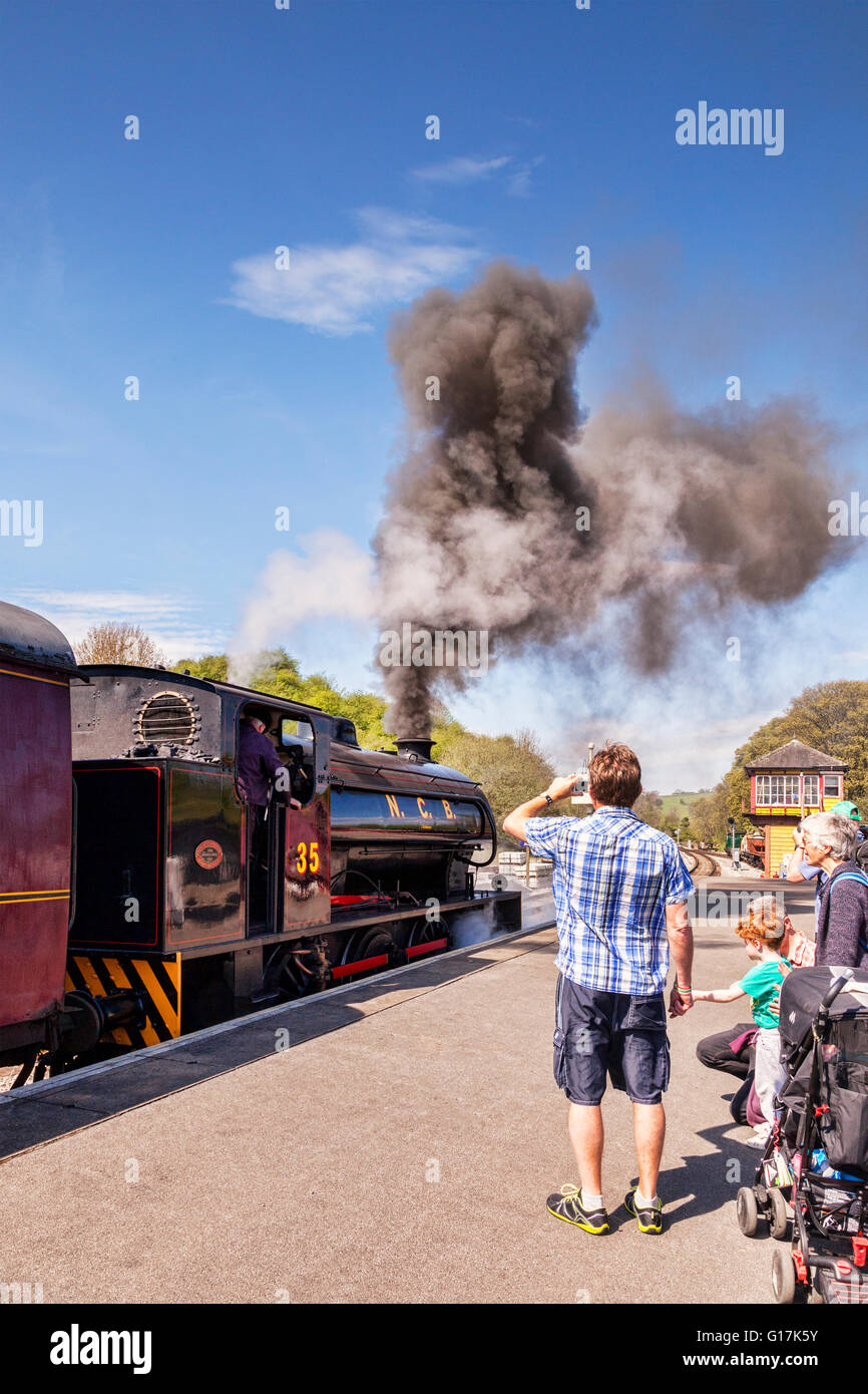 Family watch and take photos at Bolton Abbey Station, as 0-6-0 Austerity Class Saddle Tank Engine blows steam as - Stock Image