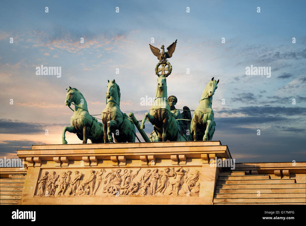 Quadriga and Bas-Relief on top of the Brandenburg Gate in Berlin, Germany with a sunset sky Stock Photo